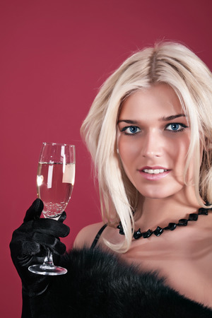 Portrait of the fine woman in an evening dress with a wine glass on a red background photo