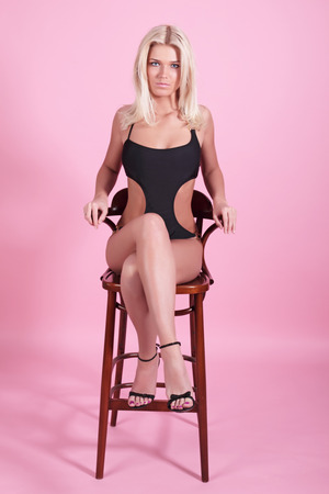 The girl in a black bathing suit sits on a bar chair on a pink background photo