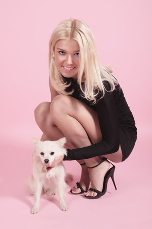 doggie: The girl squats and holds the small doggie on a pink background