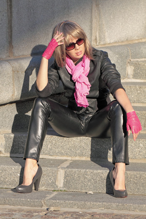 The girl in a black leather jacket and trousers sits on a granite stairs