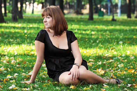 The thoughtful girl in a black dress sits in park on a grass photo