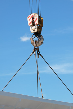 hook up: The hook of the elevating crane lifts a concrete plate against the blue sky, a close up