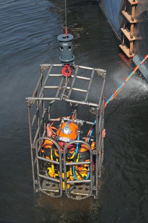 agachado: Un hombre en un equipo de buceo, alza fuera del agua en una jaula especial