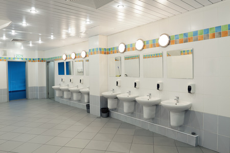 A row of washbasins with mirrors in a public toilet photo