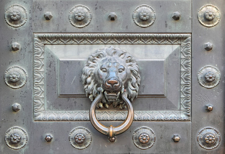 Handle antique bronze door in the form of head of a lion on a ring Stock Photo
