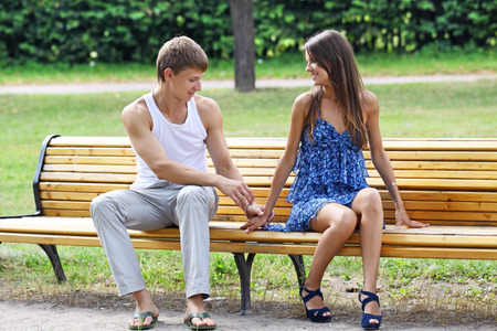 The guy and the girl on a bench in city park photo