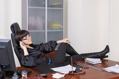 collaborator: The young girl has relaxed in an armchair at office in the end of the working day Stock Photo