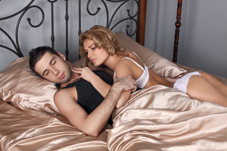 sex girl: The girl and the guy in a bed. The girl wants sexual relations, but the guy has fallen asleep