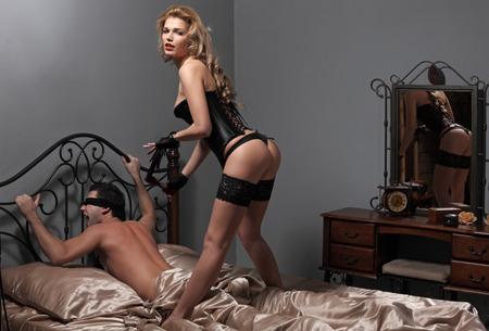 Jeune homme et la femme sont engagés dans le sexe bdsm sur un lit Banque d'images