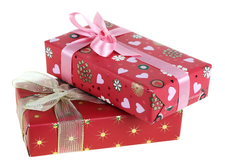 Two gift boxes which have been tied up by tapes with bows, isolated on a white background photo