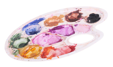 bedaubed: The plastic palette is bedaubed by multi-colored water color paints, is isolated on a white background