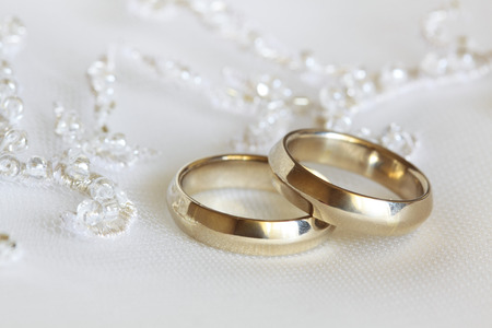 Zwei Hochzeitsringe aus Gelbgold liegen auf einem Kleid der Braut Standard-Bild - 29560906