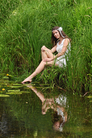 A young girl in a white dress sits on the edge of summer lake photo