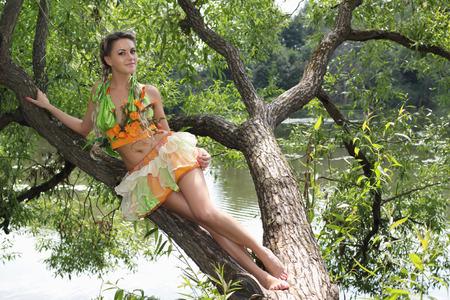 sexy girl sitting: Ragazza sexy che si siede su un albero da un fiume