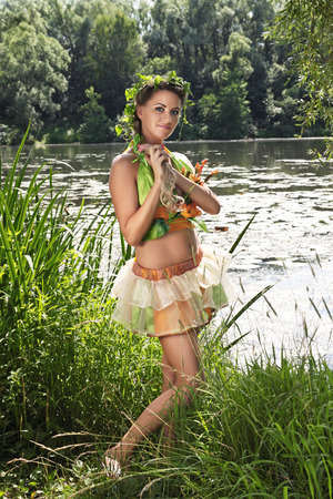 Portrait of a young girl on the bank of the river, dressed up for the holiday of Ivan Kupala (John Baptists Day) photo