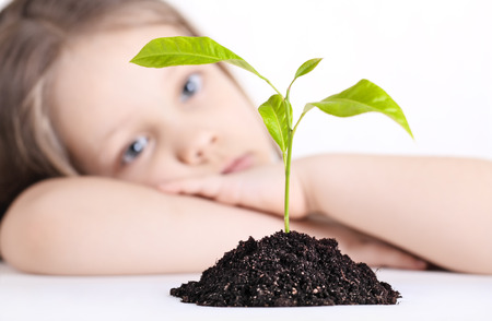 The thoughtful girl looks at a young plant photo