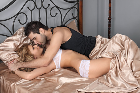 young couple sex: Heterosexual relations in a bed