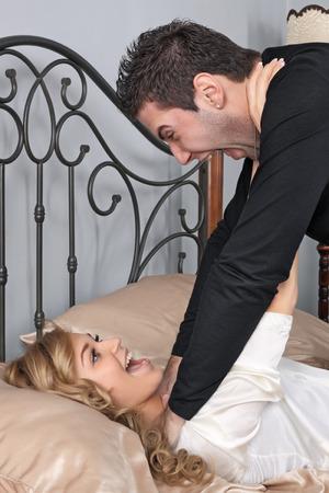 stifle: The young man smothers the young girl on a bed Stock Photo
