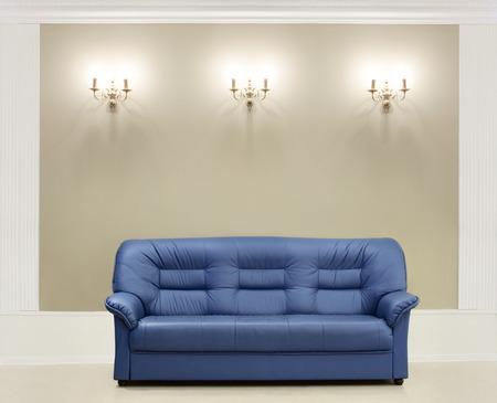 blue leather sofa: Il divano in pelle blu scuro, viene messo su un muro con candelabri Archivio Fotografico