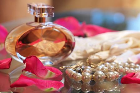 ガラス テーブルの上にバラの花びら、真珠のネックレス、香水の瓶