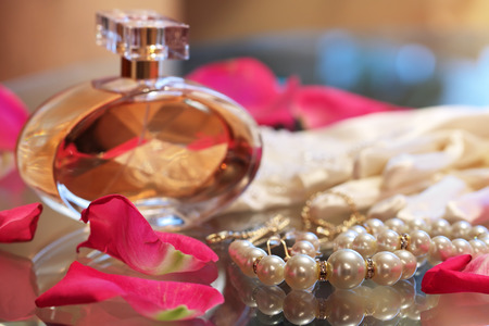 A bottle of perfume, a pearl necklace, and rose petals on the glass table