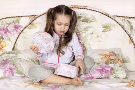 baby open present: The joyful girl sitting on a sofa opens a gift box Stock Photo