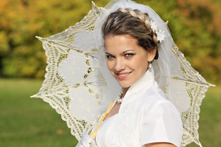 marriageable: Happy bride in a white dress with a;n umbrella sitting on the lawn in the park