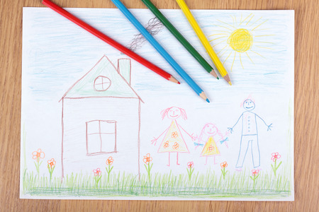 Some pencils lie in childrens drawing with the image of a happy family photo