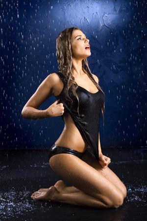 bathing costume: Portrait of the sexual young girl in a black vest in water splashes on a dark blue background