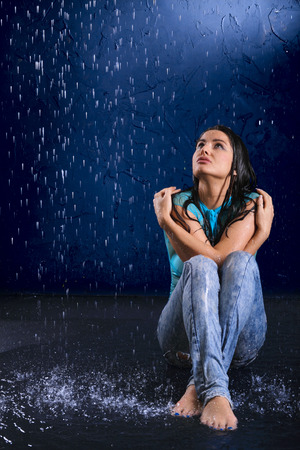 wet jeans: The blotted girl sits in the rain and looks upwards