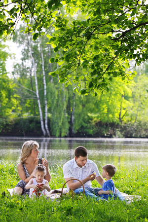 A family of four persons - father, mother, son and daughter, have a rest on the nature on the bank of the river photo