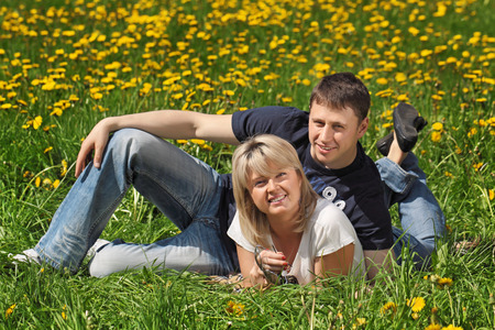 Loving couple - a boy and a girl are lying on the field with green grass and dandelions photo