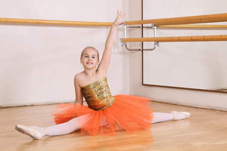 The young girl dances in a ballet orange tutu in the hall photo