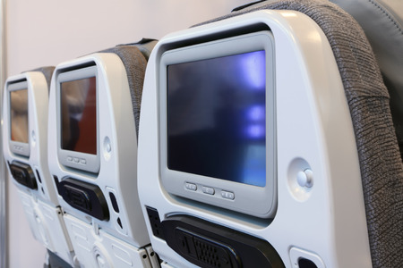 The backs of the seats in the cabin of the plane of business class with embedded in them tvs