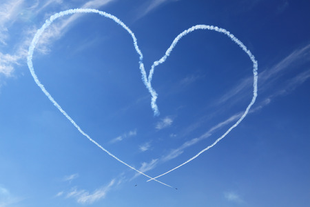 Two of the plane in the blue sky show figures of aerobatics - smoke painted heart photo