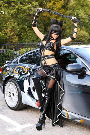 A young girl in sexy dress with a whip stands near the car