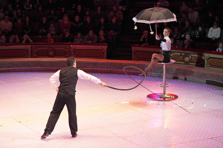 keeps: MOSCOW, RUSSIA - NOVEMBER 27: The presentation of the Golden Buff. The man knocks whip flowers with an umbrella, which keeps a woman of the Moscow State Circus on November 27, 2011 in Moscow, Russia