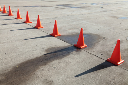 A row of orange traffic cones set on the road Stock Photo