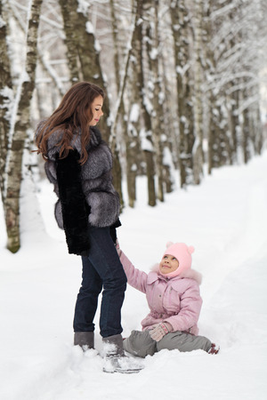 A happy mother walking with her daughter in winter Park photo
