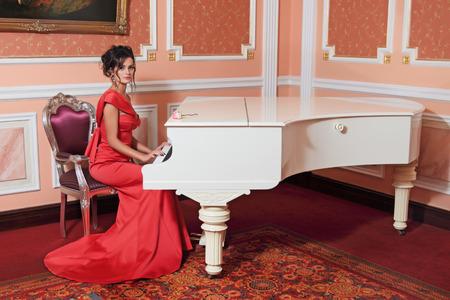 pianista: Una chica joven y bella en un vestido de noche rojo se sienta en el piano de cola Foto de archivo