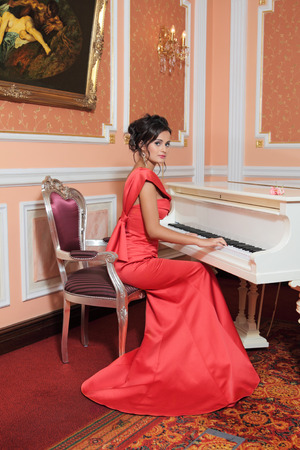 A young beautiful girl in a red evening dress sits at the grand piano photo
