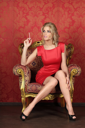 A beautiful woman is sitting with cigarette in a antique chair against the red wall
