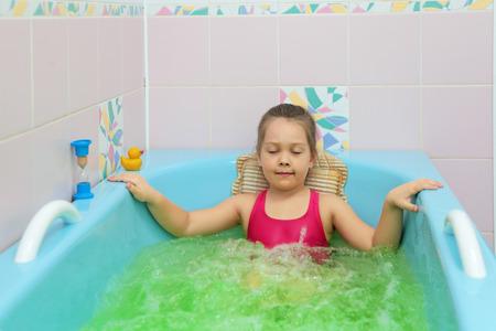 어린 소녀는 요양소에 소금 목욕을 걸립니다 스톡 콘텐츠