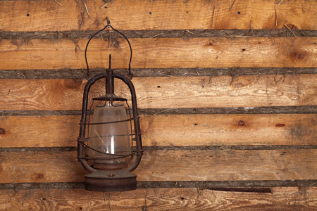 oil lamp: The old kerosene lamp hanging on the wall of a wooden house