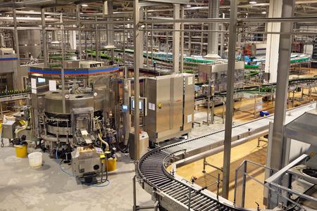 asamblea: El interior de la f�brica de cerveza. El embotellado de cerveza. Etiquetado de las botellas de la m�quina Foto de archivo