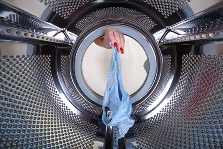 A womans hand gets blue cowards out of a drum washing machine