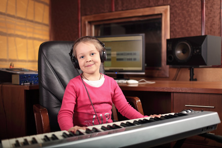 The little girl musician learns to play the on the keyboards in the Studio