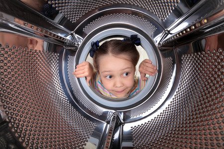 호기심이 작은 소녀는 빈 드럼 세탁기에 보이는