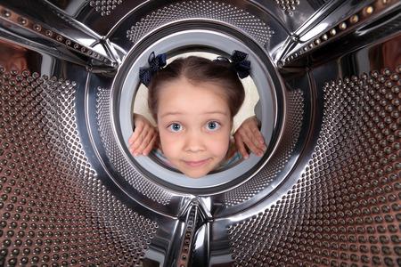 호기심 어린 소녀가 빈 드럼 세탁기를 들여다. 스톡 콘텐츠