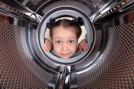 A curious little girl looks into the empty drum washing machine Stok Fotoğraf